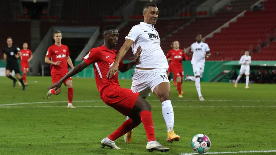 AUGSBURG, GERMANY - DECEMBER 22: Amadou Haidara of RB Leipzig battles for possession with Felix Uduokhai of Augsburg  during the DFB Cup second round match between FC Augsburg and RB Leipzig at WWK-Arena on December 22, 2020 in Augsburg, Germany. Sporting stadiums around Germany remain under strict restrictions due to the Coronavirus Pandemic as Government social distancing laws prohibit fans inside venues resulting in games being played behind closed doors. (Photo by Alexander Hassenstein/Getty Images)