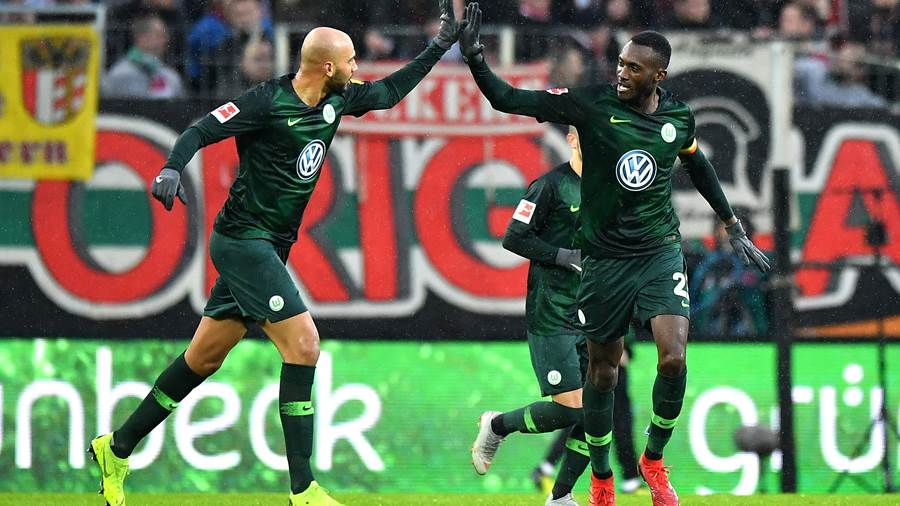 AUGSBURG, GERMANY - DECEMBER 23:  Joshua Guilavogui of Wolsfburg celebrates with John Anthony Brooks of VfL Wolfsburg after he scores his sides first goal during the Bundesliga match between FC Augsburg and VfL Wolfsburg at WWK-Arena on December 23, 2018 in Augsburg, Germany.  (Photo by Sebastian Widmann/Bongarts/Getty Images)