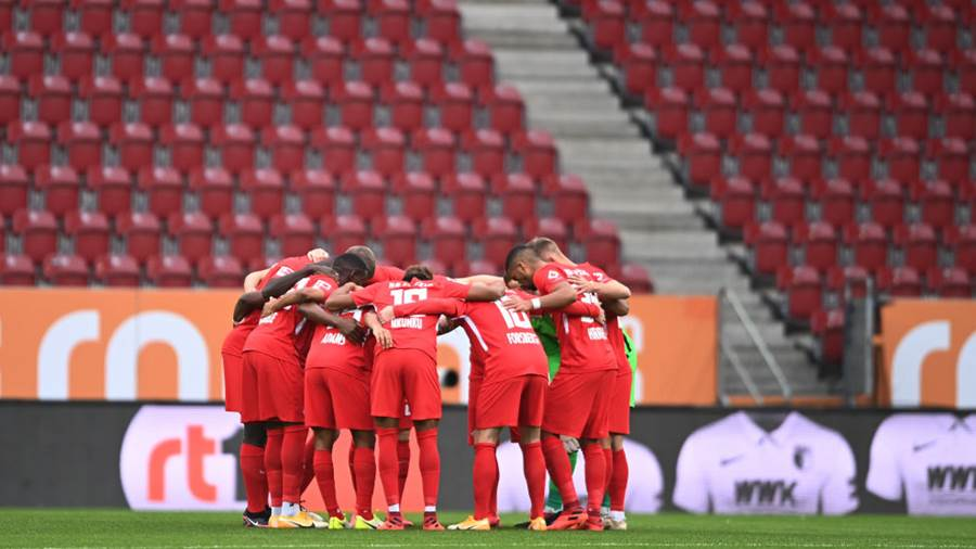 AUGSBURG, GERMANY - OCTOBER 17: Leipzig players huddle in front of empty stands before during the Bundesliga match between FC Augsburg and RB Leipzig at WWK-Arena on October 17, 2020 in Augsburg, Germany. (Photo by Lukas Barth-Tuttas - Pool/Getty Images)