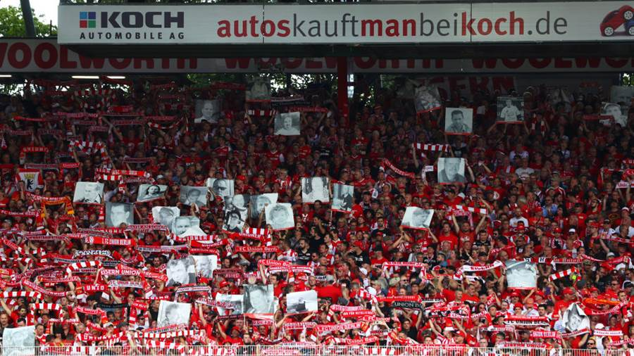 BERLIN, GERMANY - AUGUST 18:  Union Berlin fans hold posters of supporters who have passed away in the past 30 years prior to the Bundesliga match between 1. FC Union Berlin and RB Leipzig at Stadion An der Alten Foersterei on August 18, 2019 in Berlin, Germany. (Photo by Martin Rose/Bongarts/Getty Images)