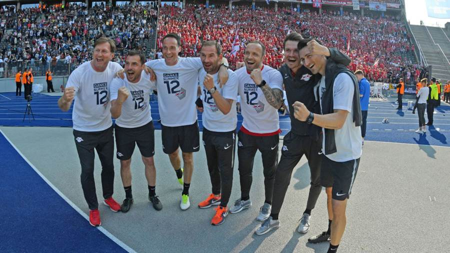 BERLIN, GERMANY - MAY 12: (EDITORS NOTE: A fisheye lens was used creating this photo) Head coach Ralph Hasenhuettl (L) of Leipzig celebrates with his stuff members after the Bundesliga match between Hertha BSC and RB Leipzig at Olympiastadion on May 12, 2018 in Berlin, Germany. (Photo by Thomas Starke/Bongarts/Getty Images)
