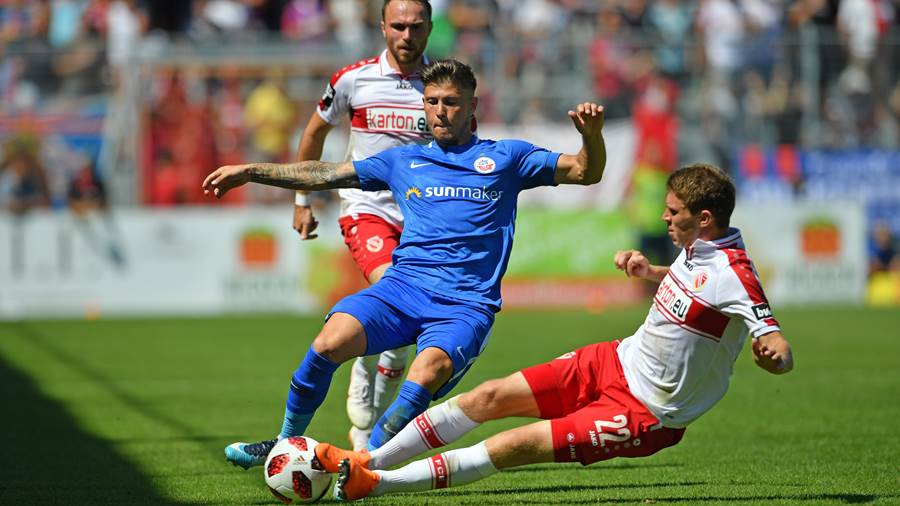 COTTBUS, GERMANY - JULY 29: Lasse Schlueter (R) of Cottbus tackles Vladimir Rankovic (C) of Rostock during the 3. Liga match between FC Energie Cottbus and F.C. Hansa Rostock at Stadion der Freundschaft on July 29, 2018 in Cottbus, Germany. (Photo by Thomas Starke/Bongarts/Getty Images)