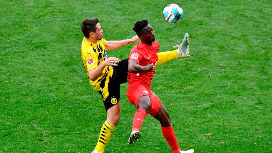 DORTMUND, GERMANY - MAY 08: Amadou Haidara of RB Leipzig is challenged by Raphael Guerreiro of Borussia Dortmund during the Bundesliga match between Borussia Dortmund and RB Leipzig at Signal Iduna Park on May 08, 2021 in Dortmund, Germany. Sporting stadiums around Germany remain under strict restrictions due to the Coronavirus Pandemic as Government social distancing laws prohibit fans inside venues resulting in games being played behind closed doors. (Photo by Martin Meissner - Pool/Getty Images