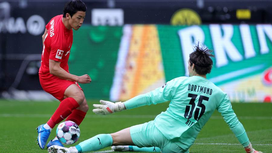 DORTMUND, GERMANY - MAY 08: Marwin Hitz of Borussia Dortmund makes  a save at the feet of Hwang Hee-chan of RB Leipzig  during the Bundesliga match between Borussia Dortmund and RB Leipzig at Signal Iduna Park on May 08, 2021 in Dortmund, Germany. Sporting stadiums around Germany remain under strict restrictions due to the Coronavirus Pandemic as Government social distancing laws prohibit fans inside venues resulting in games being played behind closed doors. (Photo by Friedemann Vogel - Pool/Getty Images)