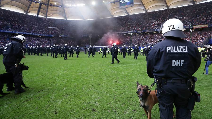 HAMBURG, GERMANY - MAY 12:  A Police dog is seen on the pitch as fans throw flares during the Bundesliga match between Hamburger SV and Borussia Moenchengladbach at Volksparkstadion on May 12, 2018 in Hamburg, Germany.  (Photo by Alex Grimm/Bongarts/Getty Images)