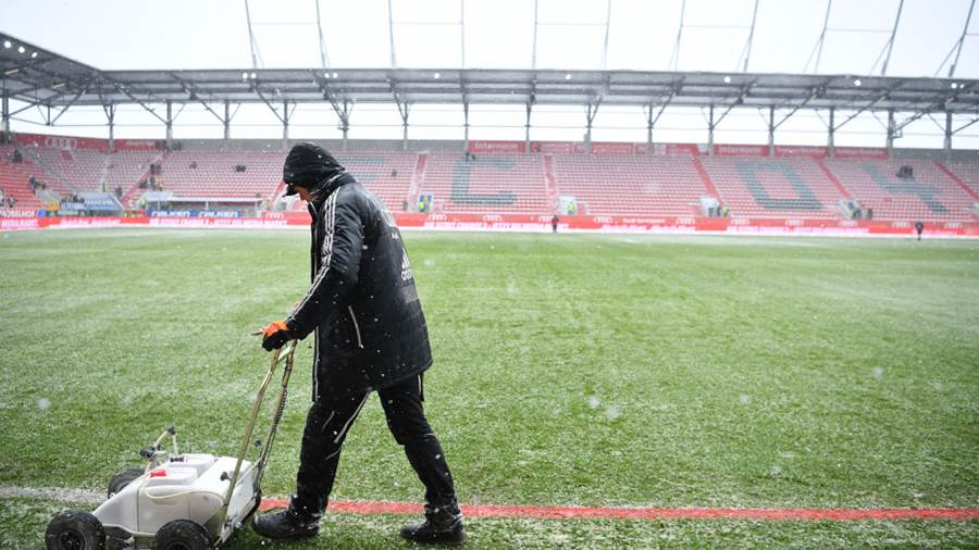 INGOLSTADT, GERMANY - MARCH 18: A worker is painting the sideline red due to snow fall prior to the Second Bundesliga match between FC Ingolstadt 04 and SG Dynamo Dresden at Audi Sportpark on March 18, 2018 in Ingolstadt, Germany. (Photo by Sebastian Widmann/Bongarts/Getty Images)