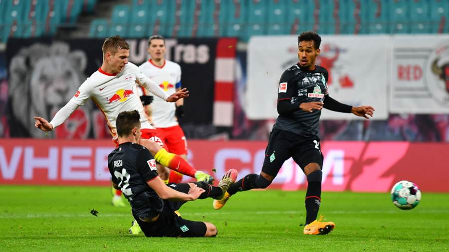 LEIPZIG, GERMANY - DECEMBER 12: Dani Olmo of RB Leipzig scores their team's second goal  under pressure from Marco Friedl of Werder Bremen  during the Bundesliga match between RB Leipzig and SV Werder Bremen at Red Bull Arena on December 12, 2020 in Leipzig, Germany. Sporting stadiums around Germany remain under strict restrictions du to the Coronavirus Pandemic as Government social distancing laws prohibit fans inside venues resulting in games being played behind closed doors. (Photo by Stuart Franklin/Getty Images)