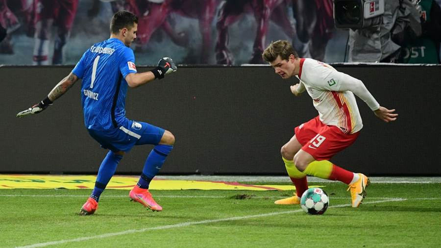 LEIPZIG, GERMANY - FEBRUARY 12: Alexander Sorloth of RB Leipzig beats Rafal Gikiewicz of Augsburg during the Bundesliga match between RB Leipzig and FC Augsburg at Red Bull Arena on February 12, 2021 in Leipzig, Germany. Sporting stadiums around Germany remain under strict restrictions due to the Coronavirus Pandemic as Government social distancing laws prohibit fans inside venues resulting in games being played behind closed doors. (Photo by Clemens Bilan - Pool/Getty Images)