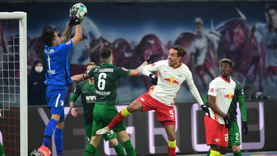 LEIPZIG, GERMANY - FEBRUARY 12: Rafal Gikiewicz of Augsburg catches the ball under pressure from Yussuf Poulsen of RB Leipzig during the Bundesliga match between RB Leipzig and FC Augsburg at Red Bull Arena on February 12, 2021 in Leipzig, Germany. Sporting stadiums around Germany remain under strict restrictions due to the Coronavirus Pandemic as Government social distancing laws prohibit fans inside venues resulting in games being played behind closed doors. (Photo by Clemens Bilan - Pool/Getty Images)