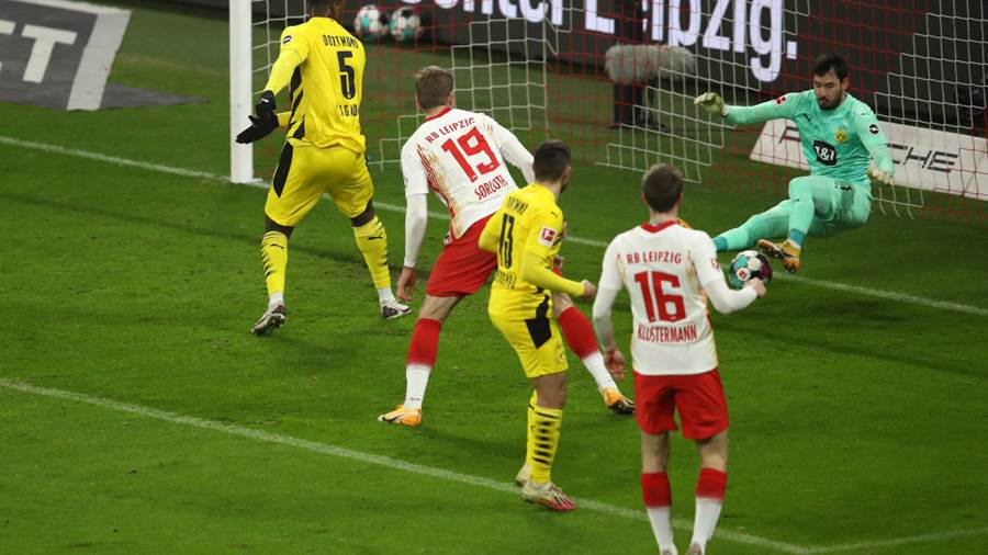 LEIPZIG, GERMANY - JANUARY 09: Alexander Sorloth of RB Leipzig scores their sides first goal past Roman Burki of Borussia Dortmund during the Bundesliga match between RB Leipzig and Borussia Dortmund at Red Bull Arena on January 09, 2021 in Leipzig, Germany. Sporting stadiums around Germany remain under strict restrictions due to the Coronavirus Pandemic as Government social distancing laws prohibit fans inside venues resulting in games being played behind closed doors. (Photo by Maja Hitij/Getty Images)