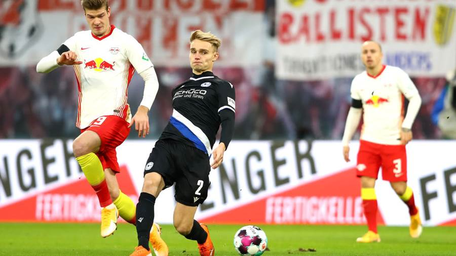 LEIPZIG, GERMANY - NOVEMBER 28: Alexander Sorloth of RB Leipzig is challenged by Amos Pieper of DSC Arminia Bielefeld during the Bundesliga match between RB Leipzig and DSC Arminia Bielefeld at Red Bull Arena on November 28, 2020 in Leipzig, Germany. Football Stadiums around Europe remain empty due to the Coronavirus Pandemic as Government social distancing laws prohibit fans inside venues resulting in fixtures being played behind closed doors. (Photo by Martin Rose/Getty Images)