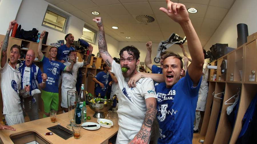 MAGDEBURG, GERMANY - APRIL 21:  (EDITORS NOTE: This image was shot with a fisheye lens.) Dennis Erdmann (C) and Felix Lohkemper (R) of 1. FC Magdeburg celebrate their promotion to Second Bundesliga after the 3. Liga match between 1. FC Magdeburg and SC Fortuna Koeln at MDCC-Arena on April 21, 2018 in Magdeburg, Germany. (Photo by Ronny Hartmann/Bongarts/Getty Images)